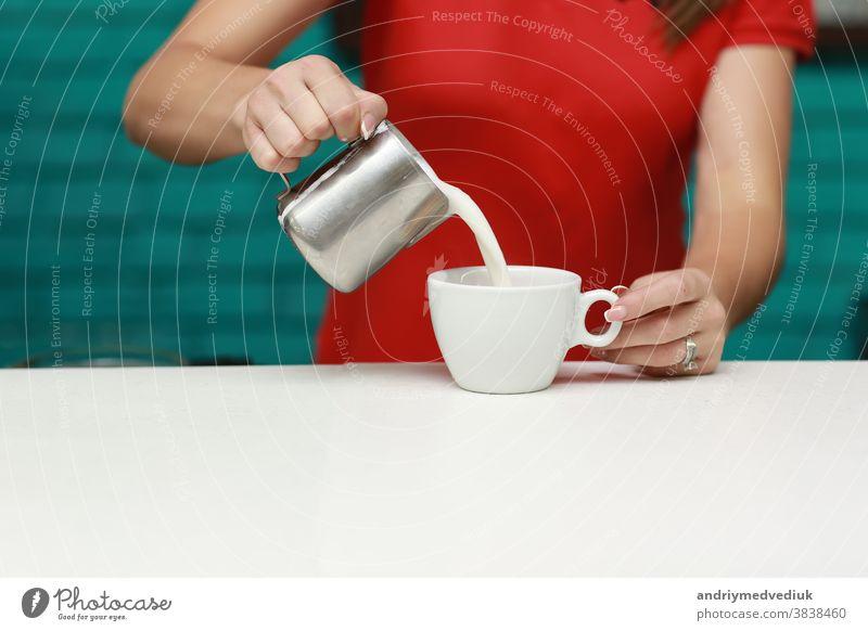 Barista bereitet in seinem Café Cappuccino zu. Nahaufnahme Kaffee Werkstatt Becher Arbeit Menschen Mann heiß Bierschaum Tasse melken Getränk eingießen machen