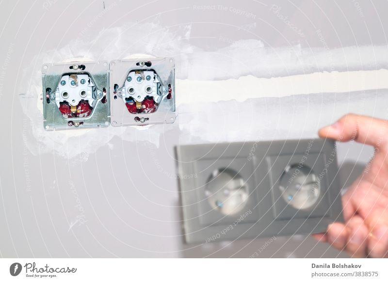 handyman entfernt den Rahmen aus der Steckdose, um das Problem zu beheben. Bild mit selektivem Fokus Appartement Bauherr Kaukasier Nahaufnahme Konstruktion diy