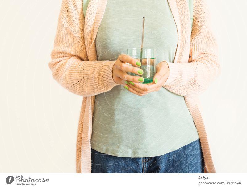 Frau hält ein Glas Wasser mit wiederverwendbarem Strohhalm keine Verschwendung Umwelt Öko trinken kunststofffrei rostfrei umweltfreundlich Pastell rosa Stahl
