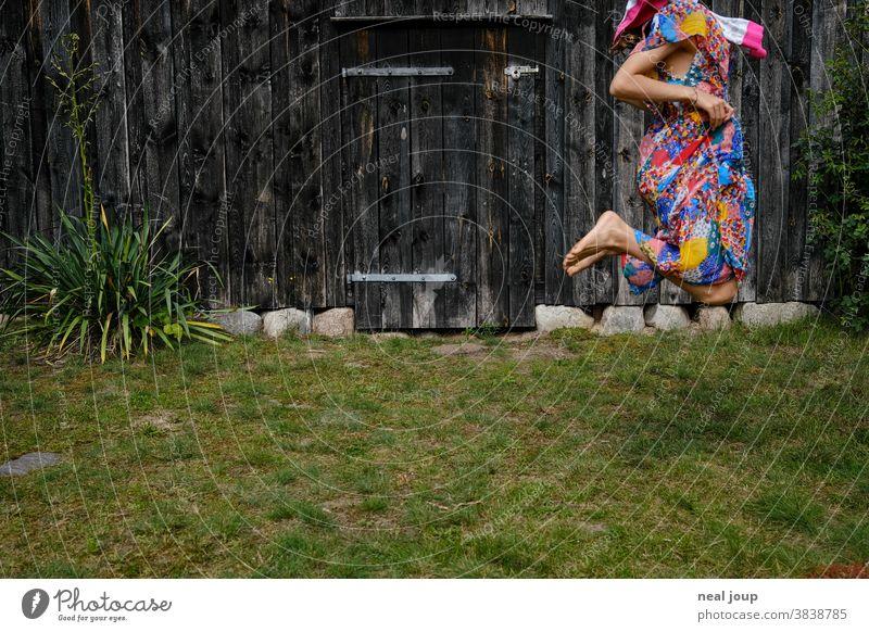 Hüpfendes Kind vor Wand einer alter Scheune hüpfen springen spielen Fröhlichkeit Spaß Spiel Verkleiden bunt Gras Rasen Garten Sommer grün angeschnitten Mädchen