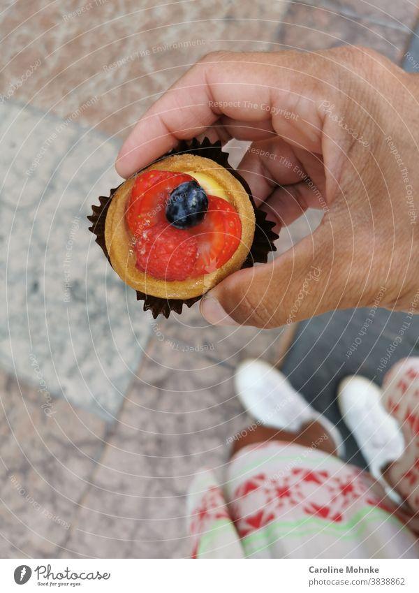 Frau hält eine kleine Süssigkeit in der Hand: Erdbeertartelette mit einer Blaubeere Dessert Erdbeere Erdbeeren Blaubeeren Frucht Lebensmittel Bioprodukte frisch