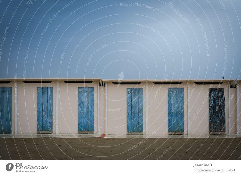 Herbststimmung, nasser Sand, Umkleidekabinen mit blauen Türen Strand Regentag leer Italien Menschenleer schlechtes Wetter Außenaufnahme Rimini Farbfoto Natur
