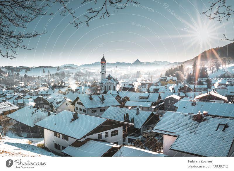 Wintermorgen über einem Bergdorf Bayern Berge Deutschland Europa Kirche Landschaftsaufnahmen Natur Nesselwang Winter 2020 Allgäu Sonnenaufgang Skyline