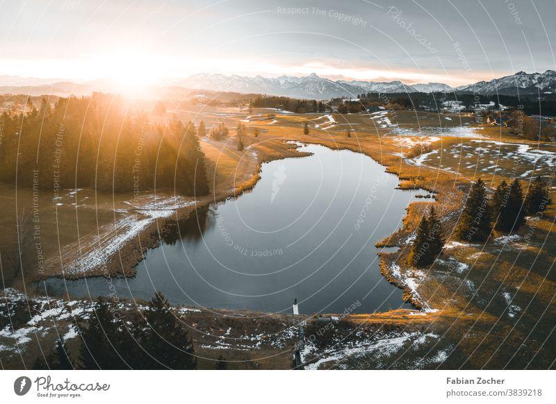 Sonnenaufgang über einem Bergsee Allgäu Bayern Berge Deutschland Drohne Europa Grundweiher Landschaft Luftaufnahme Natur See Weiher Wasser Sonnenstrahlen