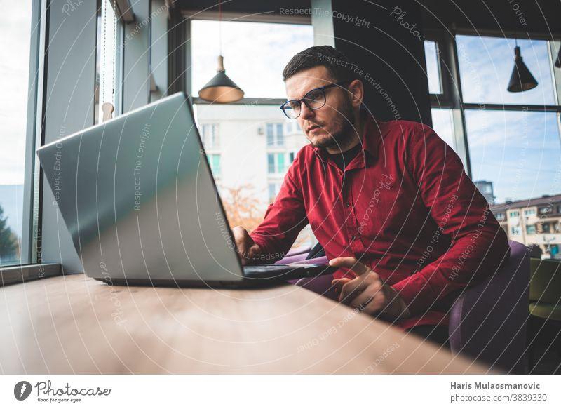 Freischaffender Mann im roten Hemd mit Brille, der am Laptop im Café arbeitet, Fernarbeit Business Geschäftsmann lässig Mitteilung Firmeninhaber Computer