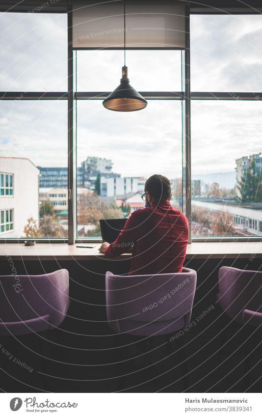 Moderner Mann Freiberufler, der vor großen Fenstern sitzt und am zurückgedrehten Laptop arbeitet Rückansicht Rückansicht Mann große Fenster Business