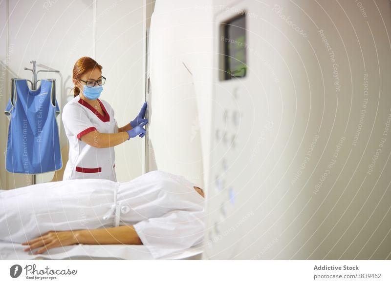 Radiologe und Patient am Tomographiegerät in der Klinik Radiologin geduldig Gerät Diagnostik Gesundheitswesen Uniform Mundschutz professionell Frauen