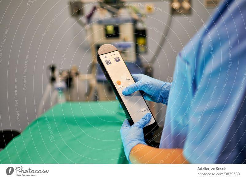 Crop Doktor mit Krankenhausbett-Fernbedienung Sanitäter Arzt Station ausrichten Gerät Arbeit Personal professionell medizinisch Kontrolle Krankenpfleger Uniform