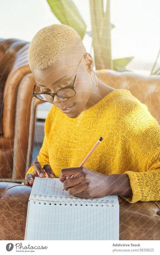 Nachdenkliche ethnische Frau macht sich Notizen im Notizblock Idee schreiben zur Kenntnis nehmen nachdenklich Denken besinnlich Memo Hinweis Terrasse schwarz