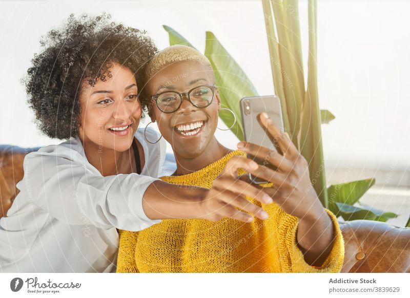 Entzücktes schwarzes lesbisches Paar, das ein Selfie auf dem Smartphone macht Frauen Liebe lgbt Selbstportrait Umarmung gleich ethnisch Afroamerikaner Mobile