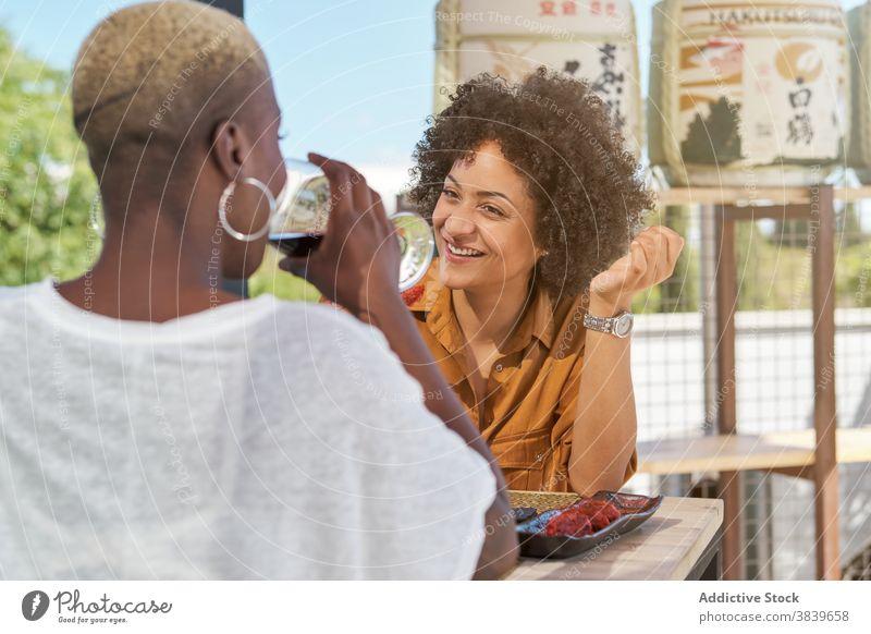 Frauen mit Weingläsern im Cafe Klirren Glas Freund Weinglas Café feiern festlich ethnisch schwarz Afroamerikaner trinken Glück heiter Terrasse Tisch Getränk