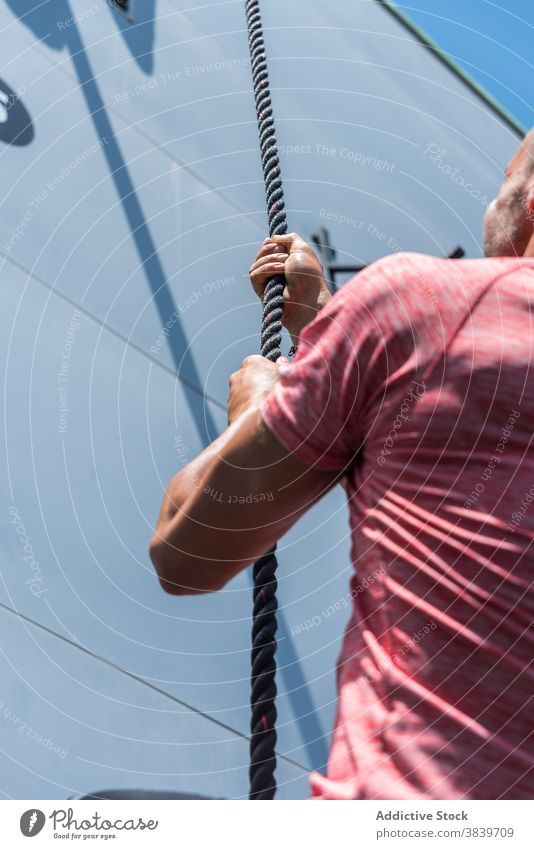 Ausdauernder Mann klettert beim Training am Seil Aufstieg Übung Sportler üben anstrengen stark männlich Athlet Gesundheit selbstbewusst Aktivität Bestimmen Sie