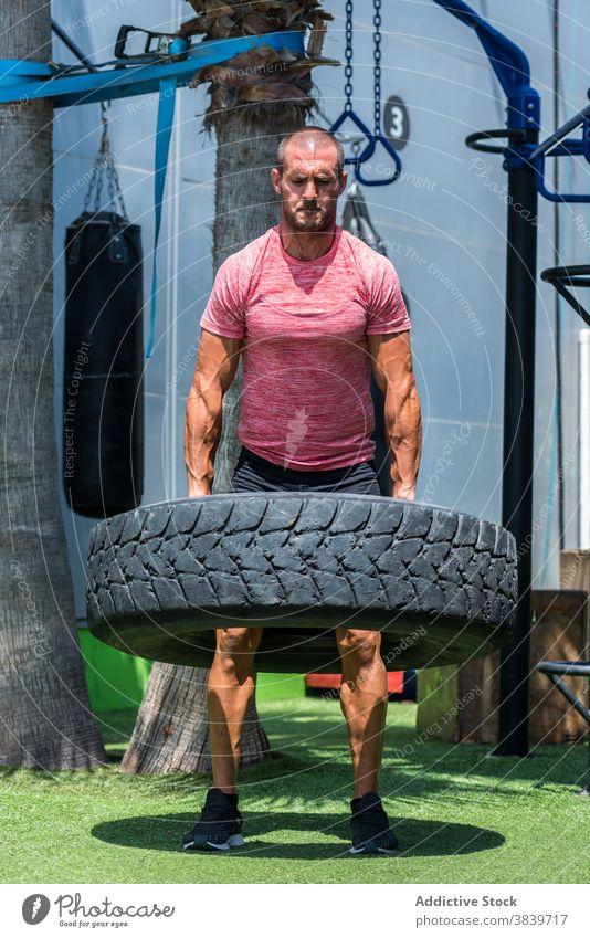 Starker Sportler bei Übungen mit schwerem Reifen Training Mann operativ stark heben Athlet männlich muskulös Kraft Gesundheit Energie Bestimmen Sie Fitness