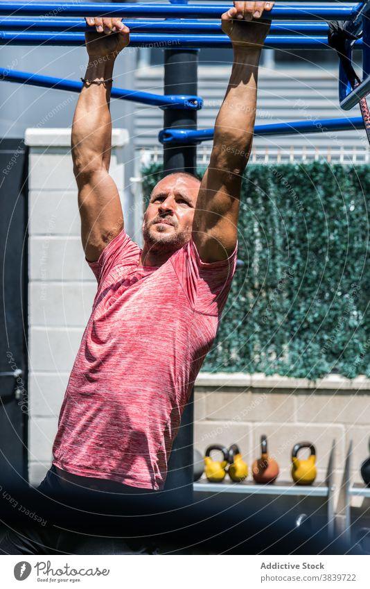 Mann, der während des Trainings auf einer Affenstange trainiert Übung Bar Sportler muskulös stark anstrengen Sportpark männlich Wellness Ausdauer passen