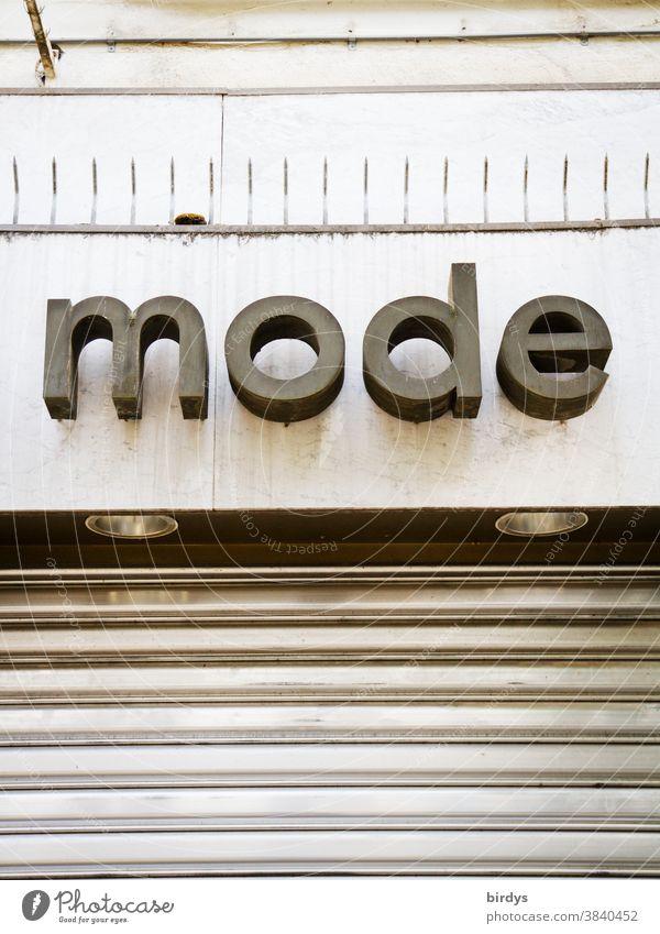 Mode. geschlossenes Bekleidungsgeschäft, Schriftzug über einer Boutique Wort Buchstaben Einzelhandel Lockdown pandemie Überleben Umsatz Krise Rollladen
