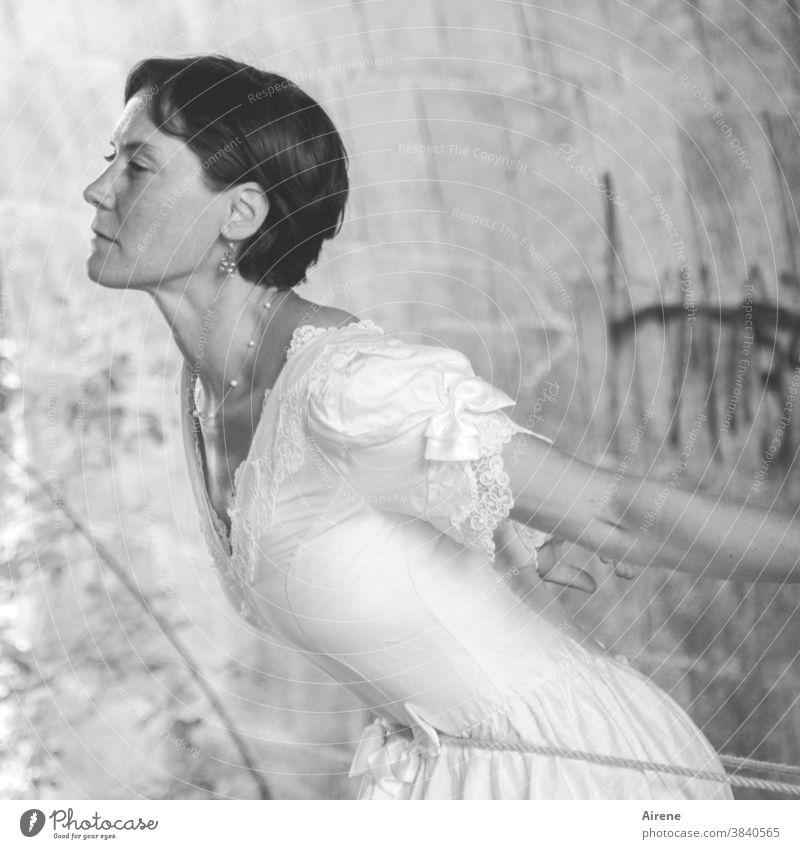 Anziehungskraft Frau attraktiv jung elegant festlich Kleid Braut Brautkleid gefangen fesseln Strick Befreiung Befreiungsversuch geneigt Flucht anziehend