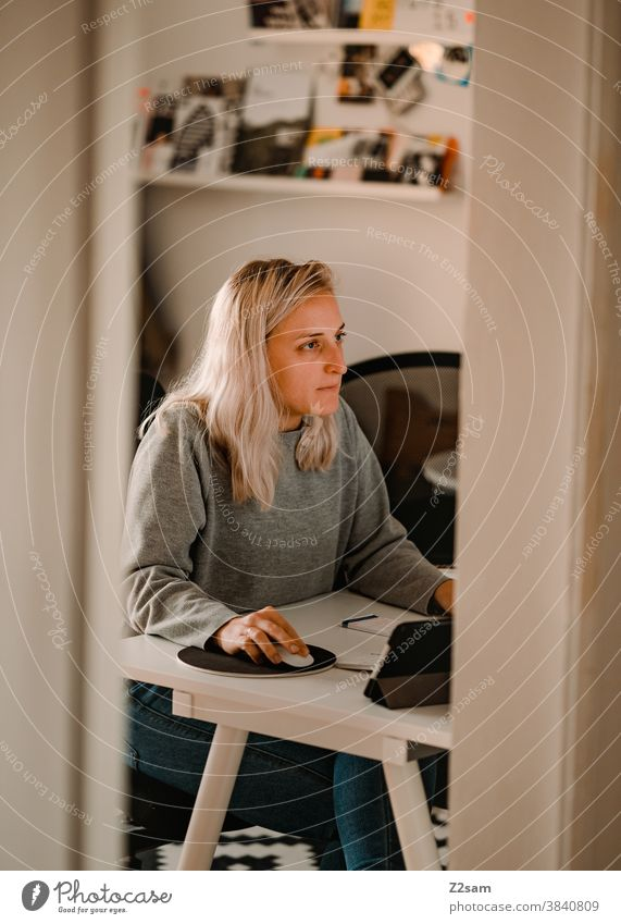 Junge Frau sitzt im Homeoffice vor dem Computer homeoffice sitzen frau junge frau blond zuhause heimarbeitsplatz schreibtisch büro computer computermaus hübsch