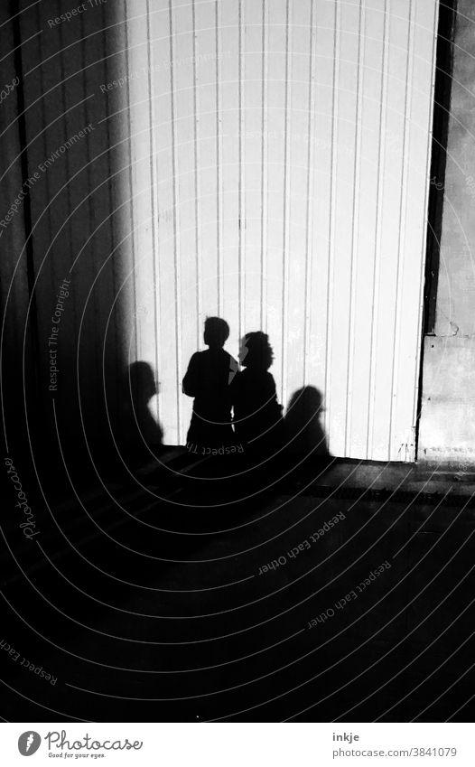 Schatten mehrerer Haushalte Schwarzweißfoto Licht Außenaufnahme Gruppe vier Personen Schlagschatten Fassade Wand trist Dunkel hell Kontrast Sonnenlicht