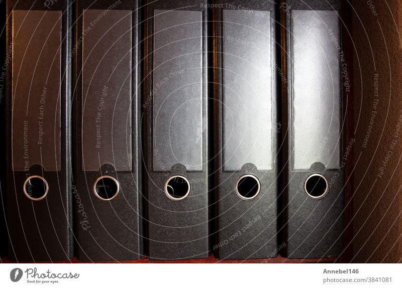 vier schwarze Ringbücher auf einem Bücherregal für Büro oder Verwaltung, Hintergrund des Geschäftskonzepts Ordner Business Mappe Orden Unternehmen Papier