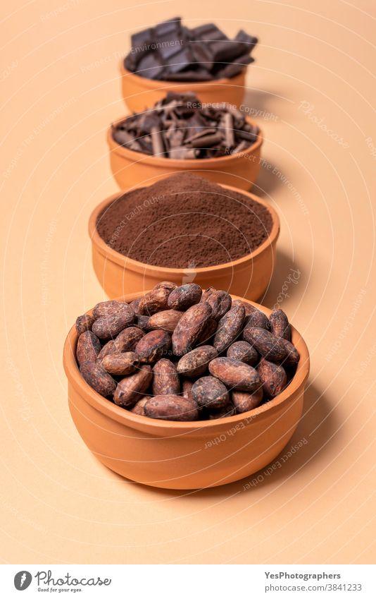 Kakaobohnen in einer Schale und isolierte Schokolade auf beigem Hintergrund Sortiment backen bitter Schüsseln Schokoladenstückchen Schokoladenstücke