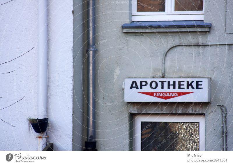 Apotheke Schriftzug Fassade Fenster Gebäude Hauswand grau verblasst Gesundheitswesen Schriftzeichen Eingang Eingangstür Tür Regenrohr Fallrohr Architektur