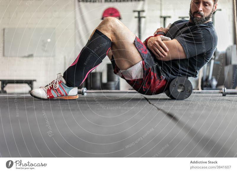 Männlicher Sportler beim Bauchmuskeltraining im Fitnessstudio Bauchmuskeln Unterleib Training knirschen Mann Gewichtheben Gewichtheber anstrengen muskulös