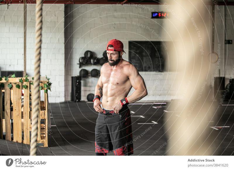 Starker Sportler mit nacktem Oberkörper im Fitnessstudio nackter Torso stark muskulös Mann Bestimmen Sie Pause Training männlich ohne Hemd Athlet Gesundheit