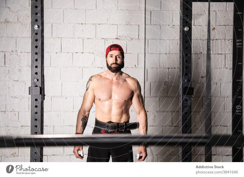 Muskulöser Sportler im Gewichthebergürtel im Fitnessstudio Gewichtheben Training Mann Gurt Gerät professionell muskulös stark männlich nackter Torso ohne Hemd