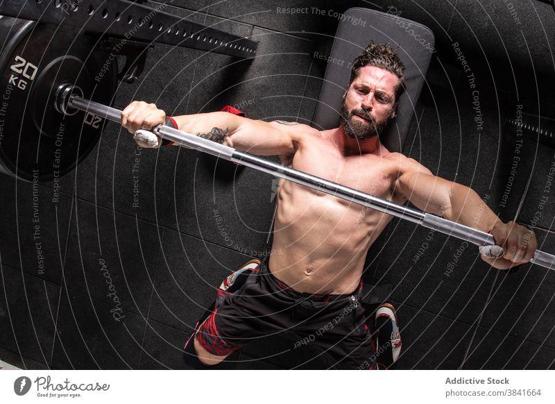 Ausdauernder Mann bei Gewichthebeübungen auf der Bankpresse Presse Übung Curl-Hantel Training Sportler Fitnessstudio anstrengen männlich Athlet Lügen stark