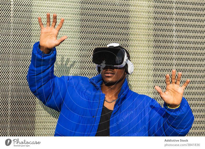 Schwarzer Mann erlebt die virtuelle Realität in der Stadt Virtuelle Realität Schutzbrille VR Brille Erfahrung interagieren berühren futuristisch Großstadt