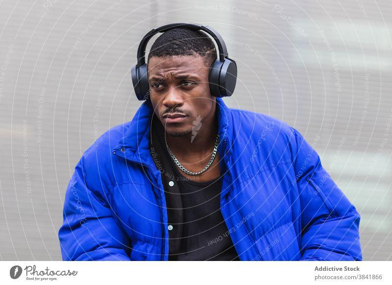 Schwarzer Mann beim Musikhören in der Stadt zuhören Windstille Gesang Kopfhörer Drahtlos Großstadt nachdenklich Melancholie Straße männlich ethnisch schwarz