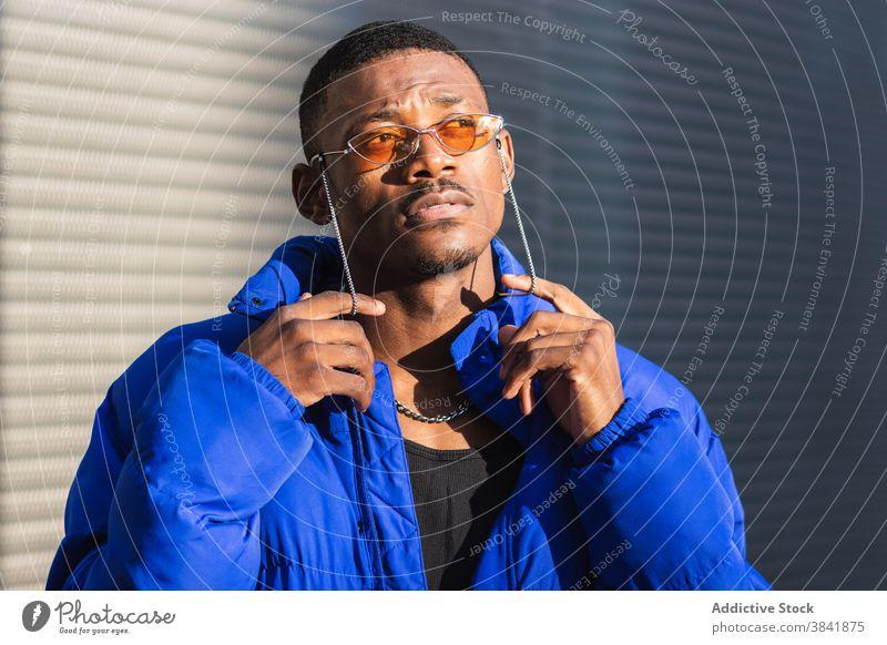 Stilvoller schwarzer Mann mit Sonnenbrille auf der Straße orange trendy Outfit Bestimmen Sie cool urban männlich ethnisch Metallwand Afroamerikaner