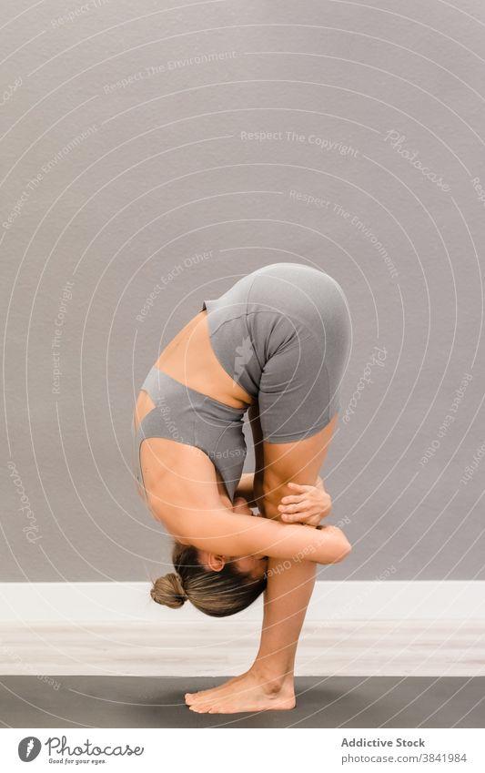 Flexible Frau stehend in Vorwärtsbeuge auf Yogamatte Asana Dehnung beweglich Unterlage uttanasana üben Barfuß Sportbekleidung passen schlank friedlich