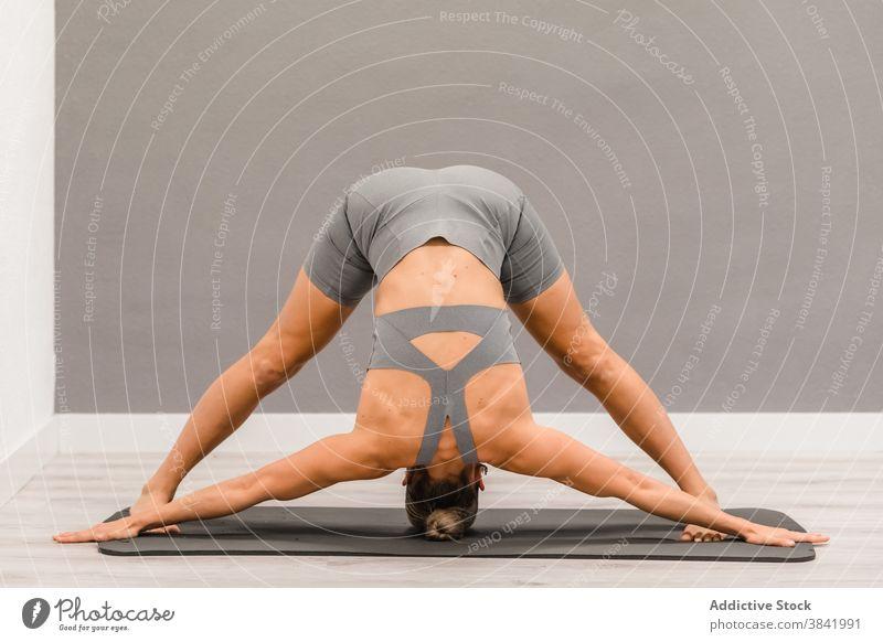 Schlanke Frau macht Yoga in Downward Facing Dog Position nach unten gerichtete Hundehaltung Yogi beweglich Dehnung Asana adho mukha svanasana Unterlage