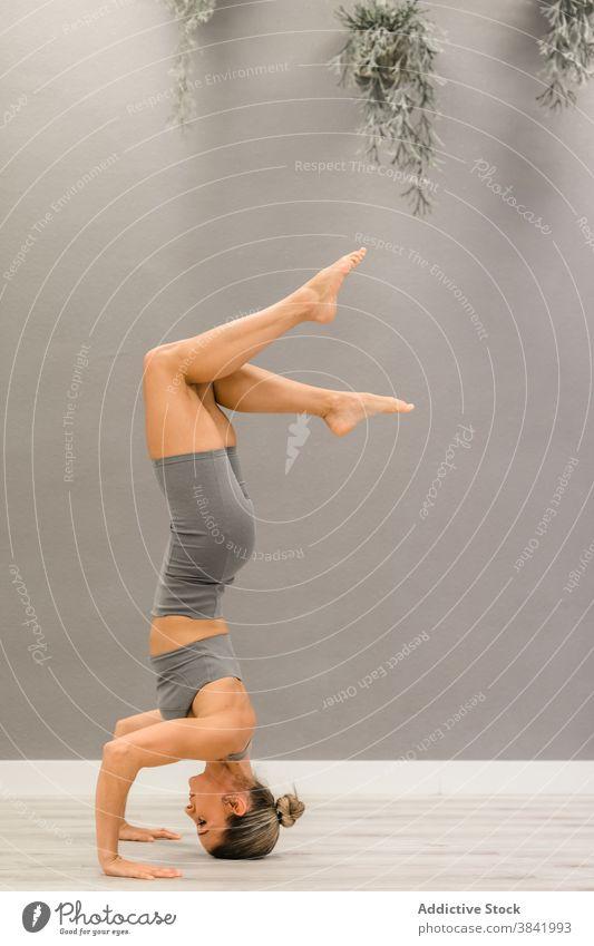 Schlanke Frau macht Yoga in Tripod Kopfstand Pose Gleichgewicht Dreibein-Kopfstand-Pose beweglich Gelassenheit Asana Salamba sirsasana Achtsamkeit üben Wellness