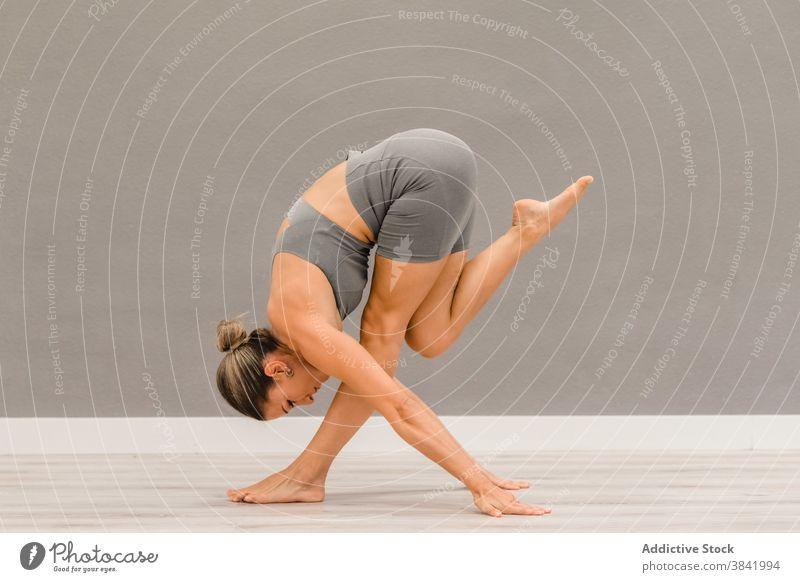 Flexible Frau übt Yoga in Vorwärtsbeuge-Pose Gleichgewicht beweglich Asana Wegbiegung Barfuß Harmonie Windstille hell Atelier passen Dehnung Wohlbefinden Körper