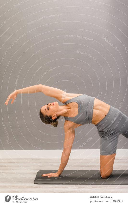 Frau übt Yoga zu Hause beweglich Asana Schiffsplanken Pose Seitenknick Unterlage Achtsamkeit ruhig sich auf die Hand lehnen Knie Gesundheit üben Harmonie passen