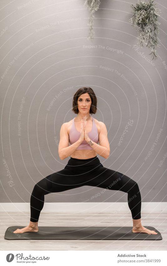 Frau in Göttin Pose tun Yoga zu Hause Göttin-Pose Ukata Konasana beweglich Unterlage heimwärts Asana Erholung Stressabbau Achtsamkeit Gesundheit üben Wellness