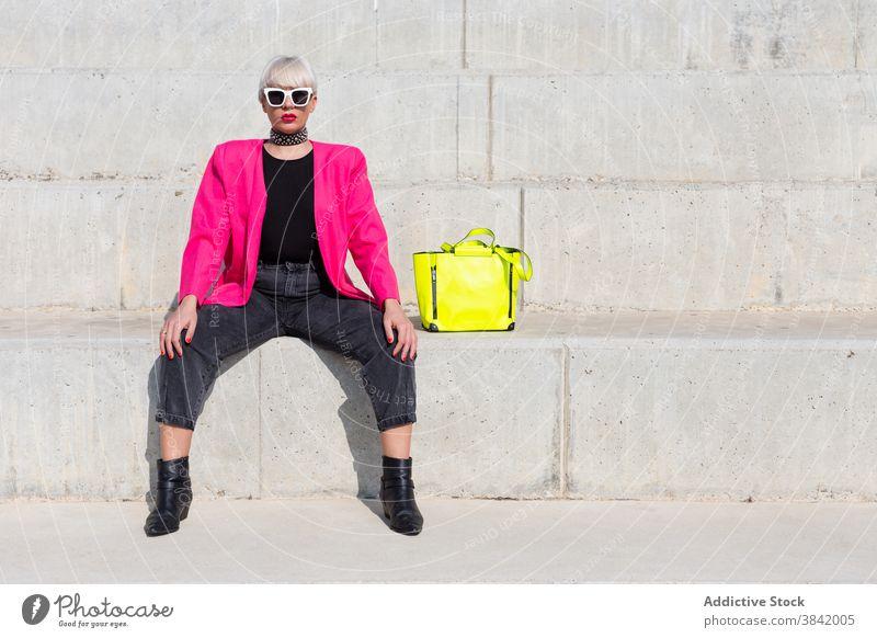 Stilvolle kreative Frau in rosa Jacke in der Stadt lebhaft Outfit Model Großstadt trendy Farbe hell gelb Handtasche Stoff Straße sitzen cool urban pulsierend