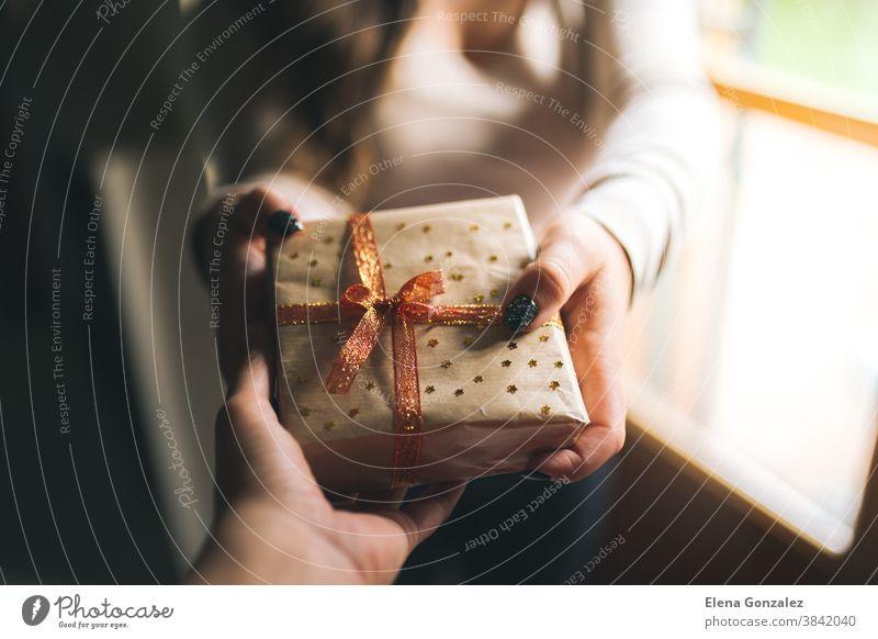 Junge Frauen mit schwarzen Glitzernägeln, die seinem Freund eine Weihnachtsgeschenkschachtel schenken. Hände halten eine Neujahrs-Geschenkschachtel, die mit Bastelpapier, rotem und goldenem Band und Sternen dekoriert ist. Familiengeschenk und Feiertagskonzept.