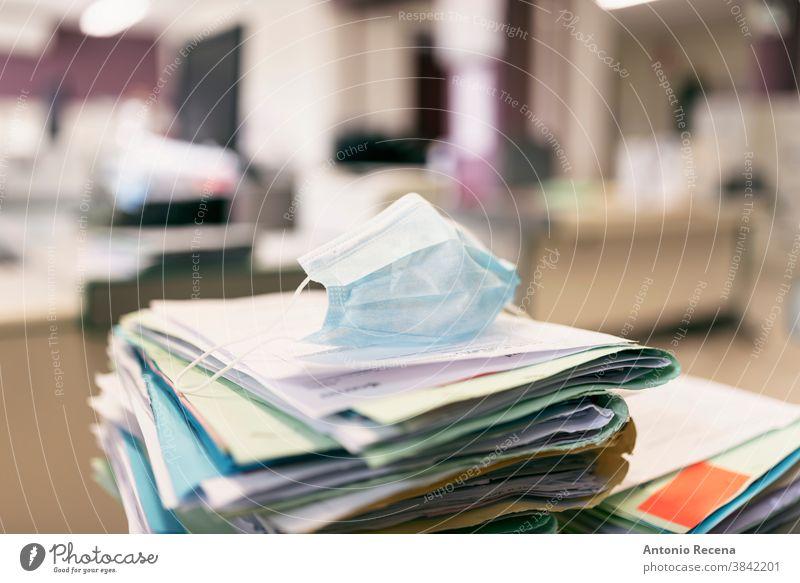 Schützende Gesichtsmaske für die Ansammlung von Papierarbeiten in Pandemiejahren covid-19 Corona-Virus Büro Arbeit keine Menschen keine Leiche Schriftstück