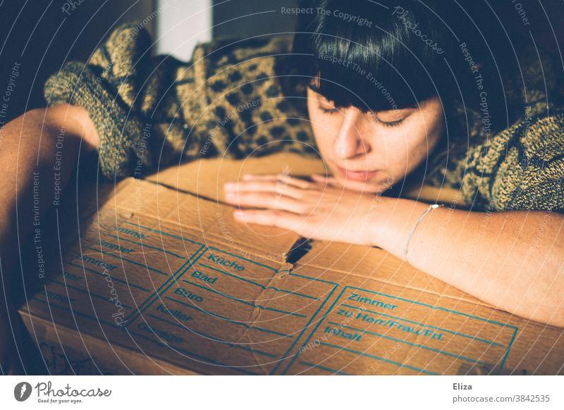 Frau liegt mit dem Kopf auf einem Umzugskarton und sieht müde aus. Wohnungsnot Eigenbedarfskündigung ausziehen wohnungslos erschöpft traurig Stress Karton