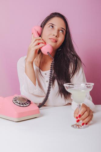 Fröhliche und lächelnde junge brünette Frau mit Getränk, benutzt ein altmodisches Telefon. Porträt auf rosa Hintergrund schön Brasilianer Einwegartikel trinken