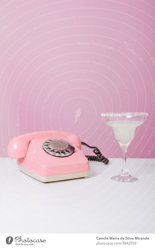 Vintage-Rosentelefon mit einem Getränk daneben. 60's 60s inserieren Hintergrund Anruf Farbe Textfreiraum Fünfziger für Text Spaß flippig Gute Neuigkeiten
