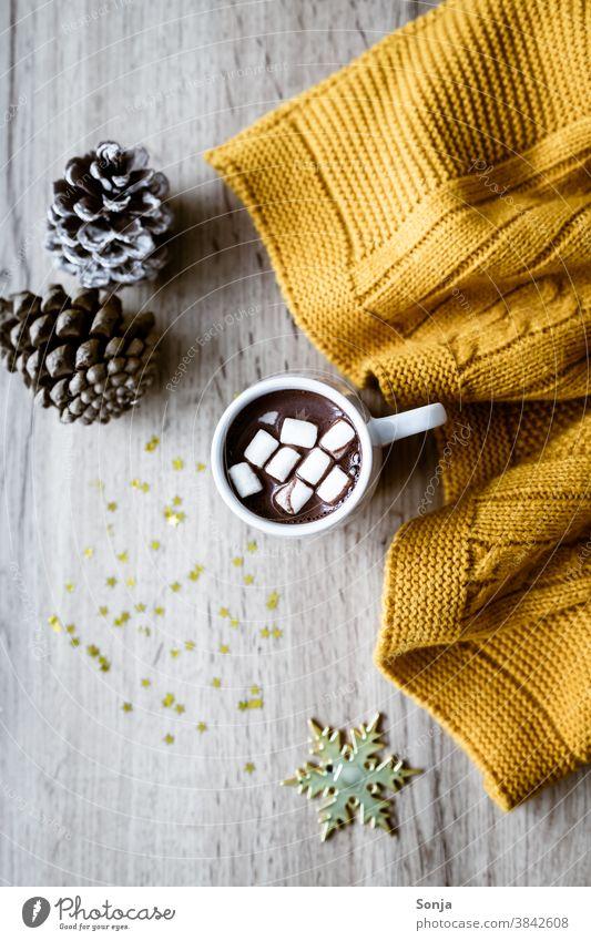 Heiße Schokolade mit Marshmellows, eine gelbe Wolldecke und goldene Sterne auf einem Holztisch. marshmellow Tasse Hygge rustikal Getränk süß Kakao Farbfoto