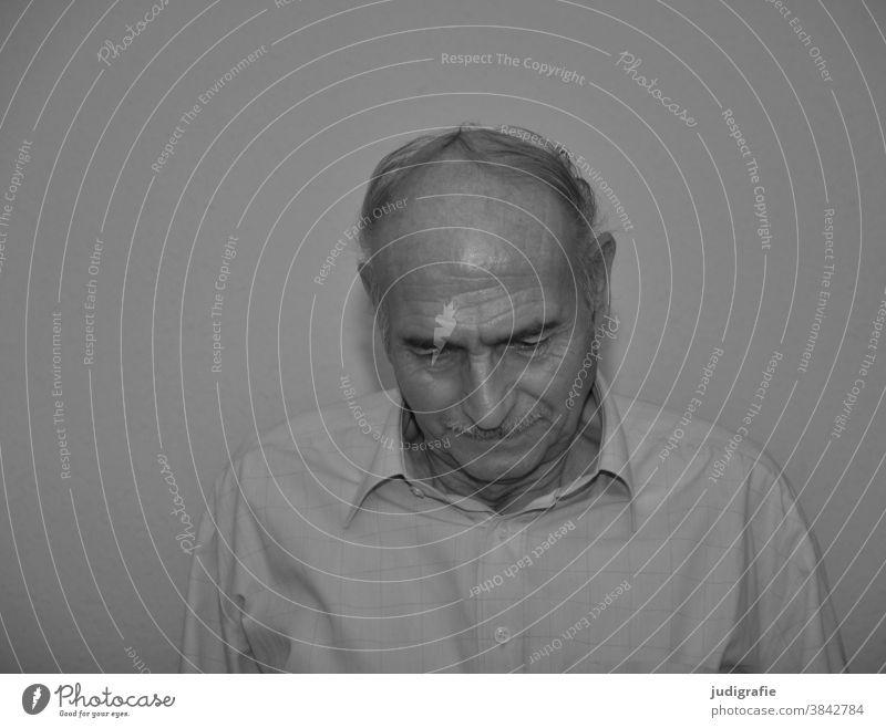 Senior schaut entspannt nach unten. Portrait Mann Männlicher Senior Großvater Erwachsene Schwarzweißfoto Leben Innenaufnahme authentisch Blick
