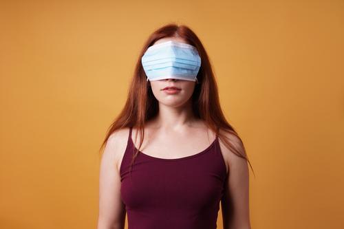 junge Frau, die Mundschutz Maske über den Augen trägt - Corona-Leugner Gesichtsmaske Korona-Verweigerer COVID Coronavirus leugnen blind falsch protestieren