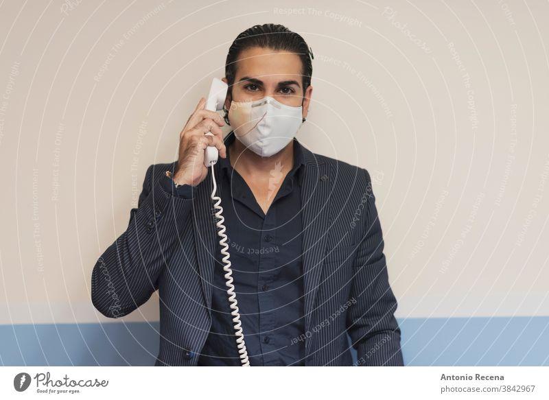 Anzugträger am Telefon schaut in die Kamera Kabel Mann covid-19 Coronavirus Business Männer Mitteilung Sale Verkäufer Telemarketing Mundschutz Chirurgie
