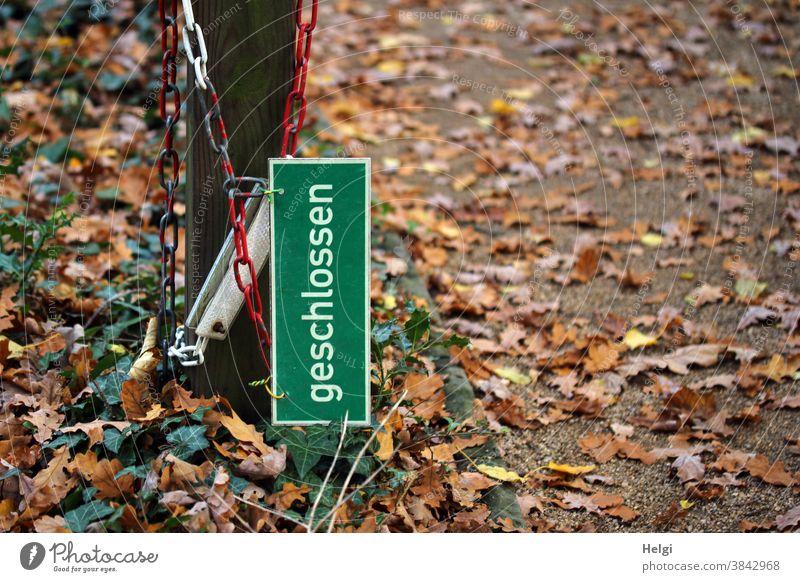 """offen - Schild """"geschlossen"""" hängt samt Absperrkette an einem Pfahl neben dem Weg, der mit Herbstlaub bedeckt ist Absperrung Blätter Laub Herbstfärbung"""