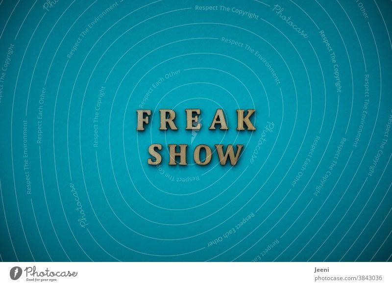 FREAKSHOW | Text auf einfarbigem Hintergrund in türkis-blau Freakshow Verrückter Durchgedrehter Mensch skuril verrückt beängstigend ungewöhnlich ausgeflippt